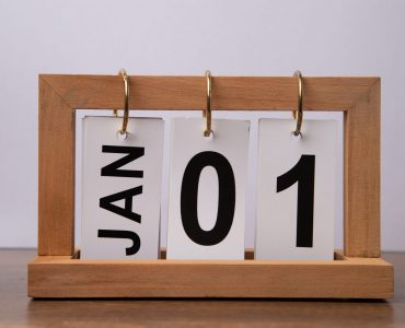 January 1st. Day 1 of january month, calendar on wooden table and white background.