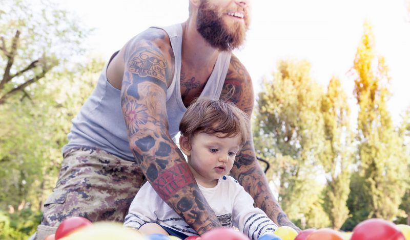 tattooed father have fun with his son in the park with colored b